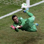 Brazil's goalkeeper Julio Cesar dives to make a save during their Confederations Cup Group A soccer match against Japan at the Estadio Nacional in Brasilia